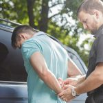 Middle aged cop putting handcuffs on drunk driver